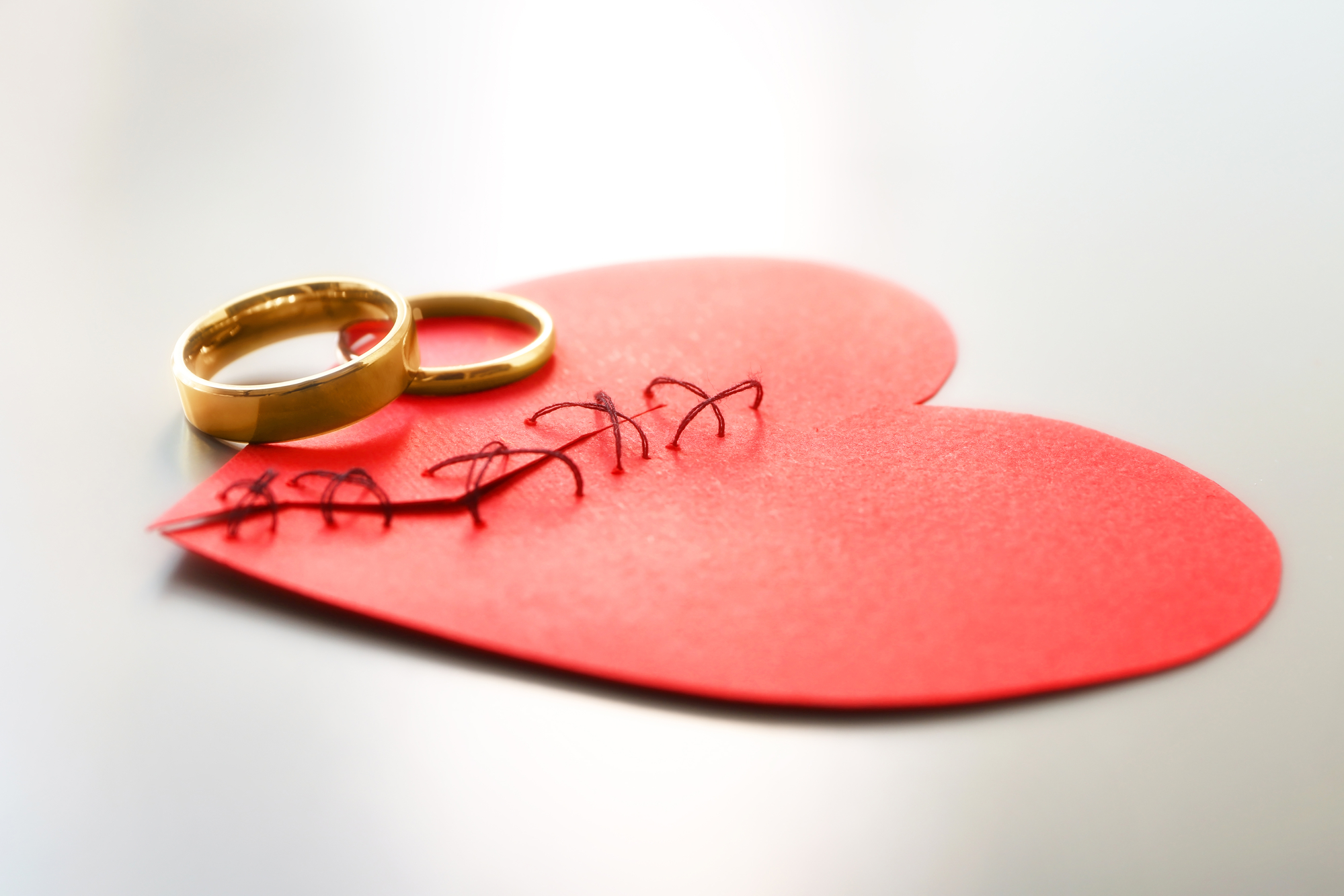 Paper heart cut in half and sewn back together with wedding rings on light background. Relationship problems
